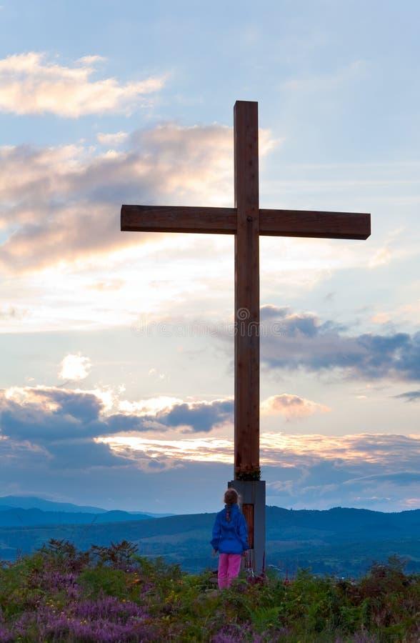 Kleines Mädchen nahe hölzernem Kreuz stockfoto