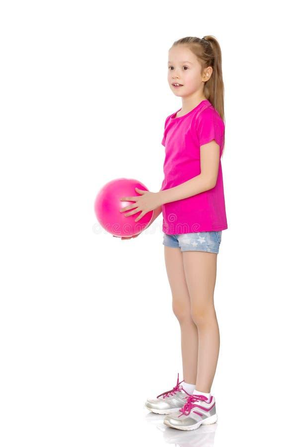 Kleines Mädchen nimmt an Eignung mit einem Ball teil lizenzfreie stockfotografie