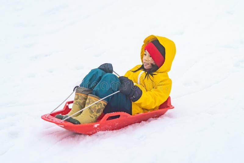 Kleines Mädchen rutscht in der Skiregion Gala Yuzawa den Schnee hinunter stockfotos
