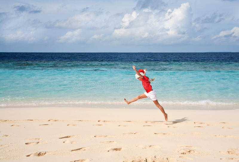 Kleines Mädchen Sankt im Hut auf dem Strand lizenzfreies stockfoto