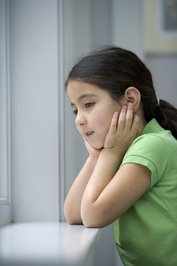 Kleines Mädchen schaut aus dem Fenster heraus lizenzfreie stockfotografie