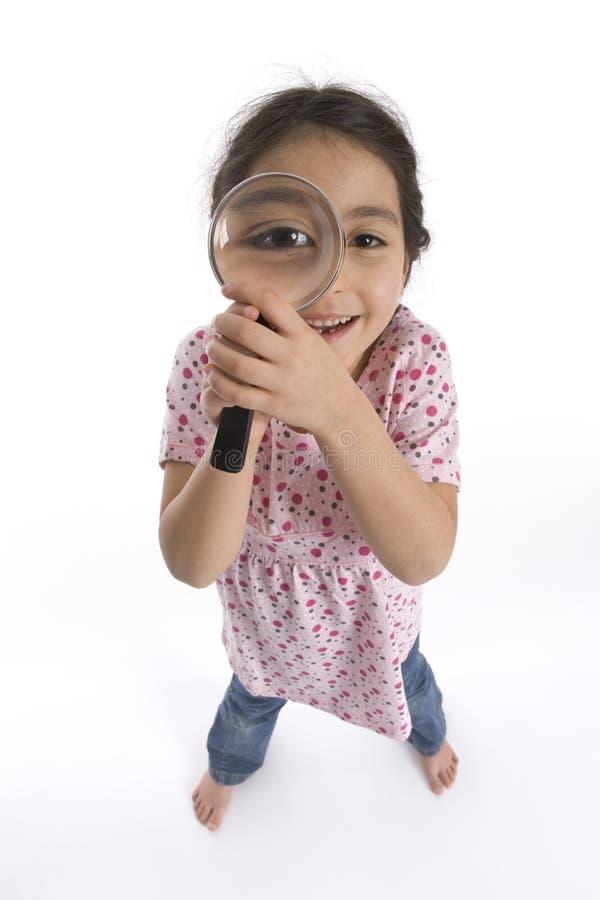 Kleines Mädchen schaut durch ein Vergrößerungsglas stockfotografie
