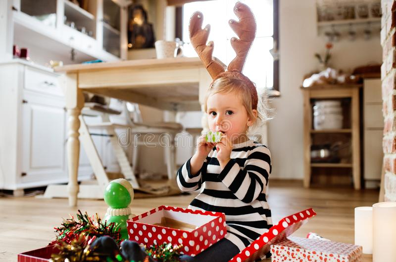 Kleines Mädchen an Schlagparteipfeife der Weihnachtszeit lizenzfreie stockfotos