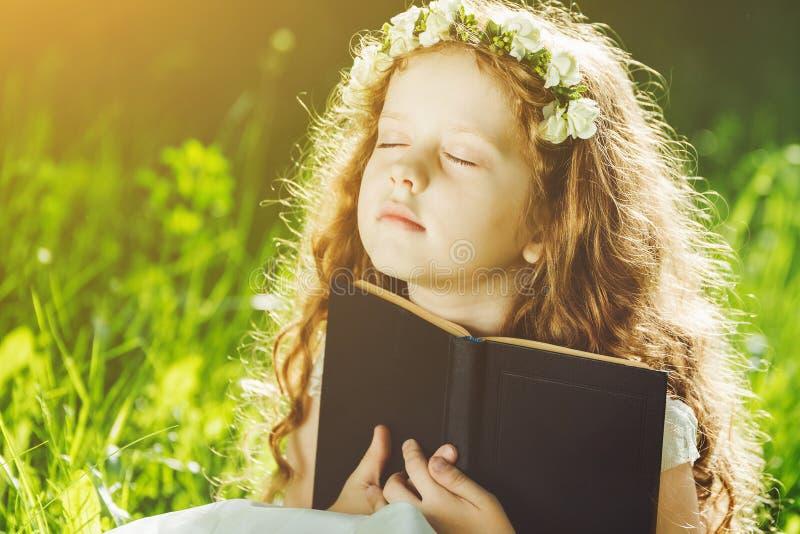 Kleines Mädchen schloss ihre Augen und betete, träumt oder liest ein Buch stockbild