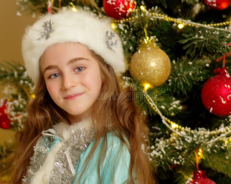 Kleines Mädchen Schnee-Mädchen nahe dem Baum des neuen Jahres stockfotos