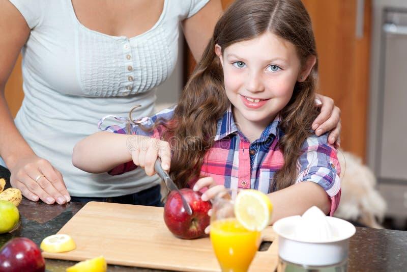 Kleines Mädchen schneidet Apfel lizenzfreie stockfotografie