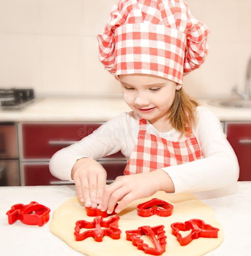 Kleines Mädchen schneidet Teig mit Form für Plätzchen lizenzfreies stockfoto