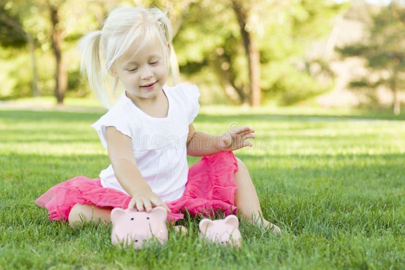 Kleines Mädchen setzt eine Münze ihre Sparschweine draußen stockfoto