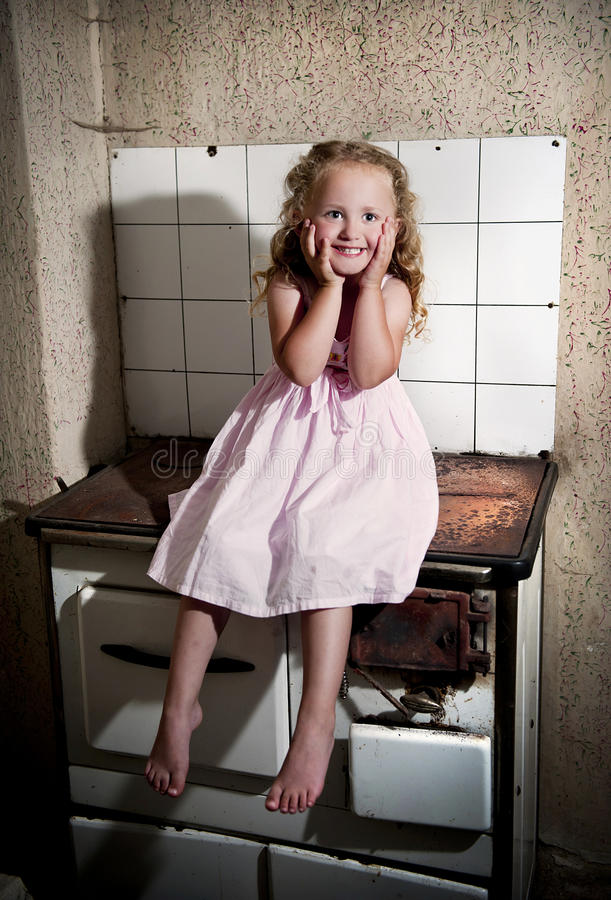 Kleines Mädchen auf dem Kocher stockfotos