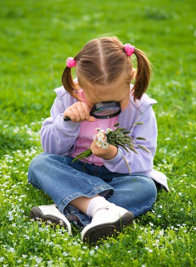 Kleines Mädchen sitzt auf grüner Wiese stockfoto