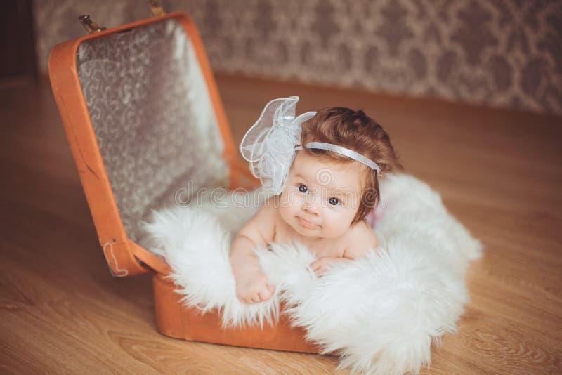 Kleines Mädchen sitzt in einem Koffer. Ein dunkler Hintergrund. lizenzfreie stockfotos
