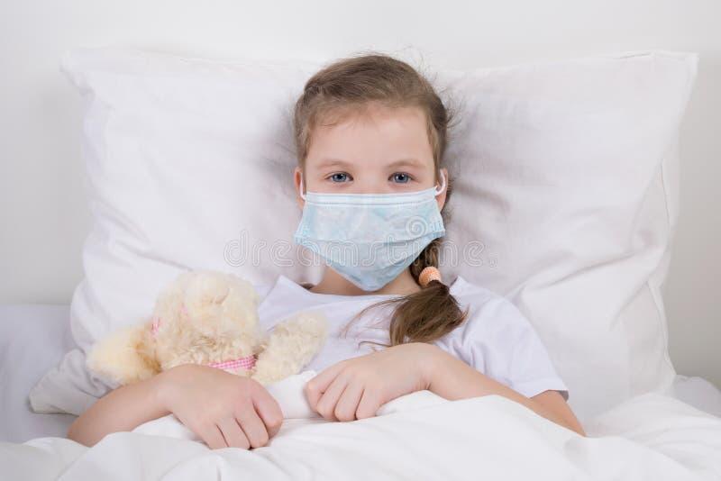 Kleines Mädchen sitzt im Bett in einer medizinischen Maske, um sich vor Infektion zu schützen stockbild