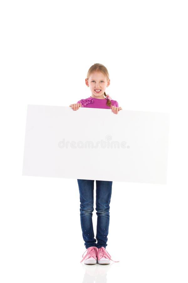 Kleines Mädchen Smilling, das mit leerer Fahne aufwirft. stockbild