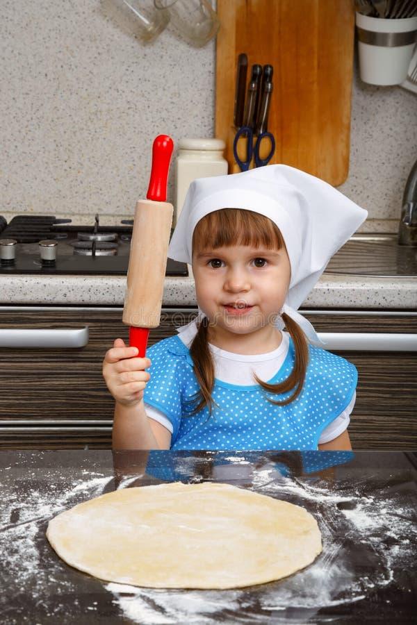 Kleines Mädchen spielt als Koch lizenzfreie stockbilder