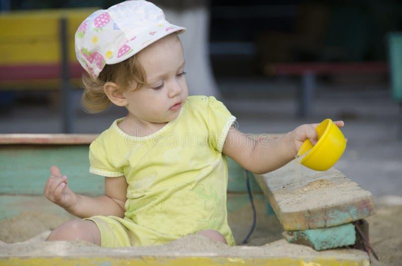Kleines Mädchen spielt im alten Sandkasten lizenzfreie stockfotos