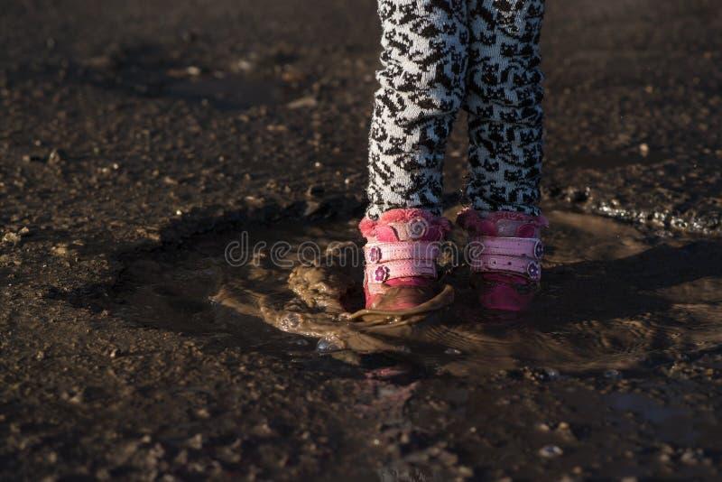 Kleines Mädchen spielt im Wasser, nasse schmutzige Schuhe, mitten in Pfütze, unvergessliche Momente, Kind-` s Unterhaltungen Conc stockfotos
