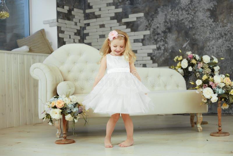 Kleines Mädchen spining im weißen Luxuskleid stockbild