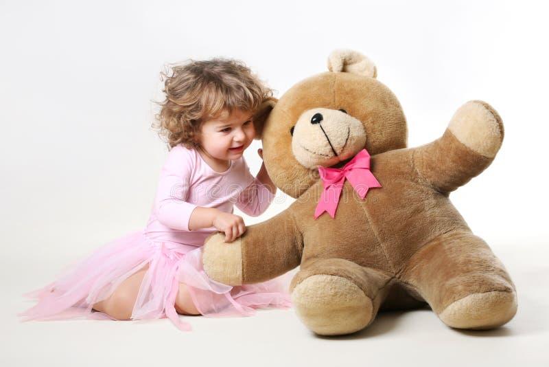 kleines Mädchen spricht mit ihrem Teddybären lizenzfreie stockfotos