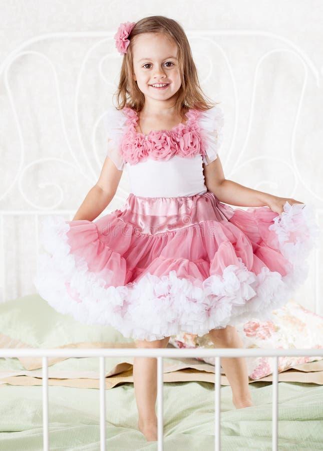Kleines Mädchen springt auf das Bett stockfotos