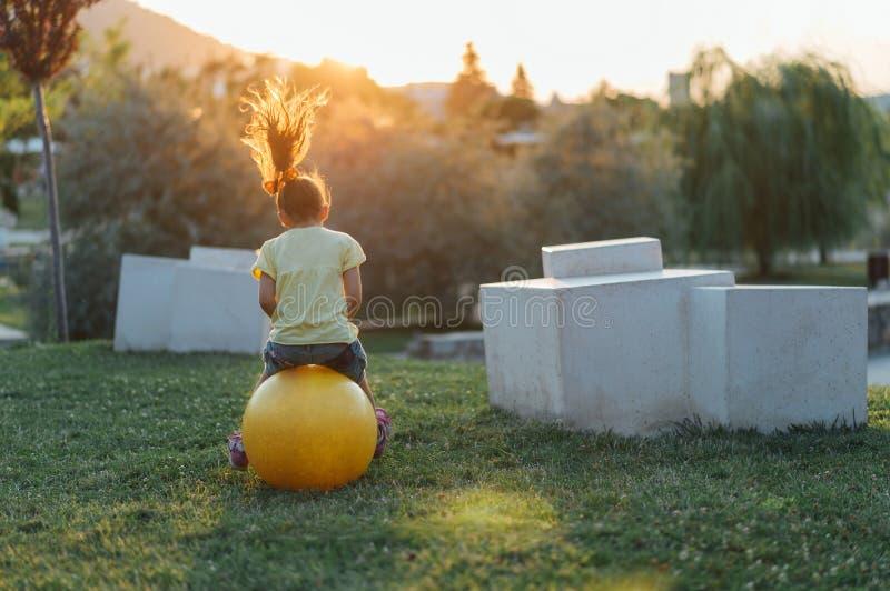 Kleines Mädchen springt auf den Ball stockfotos