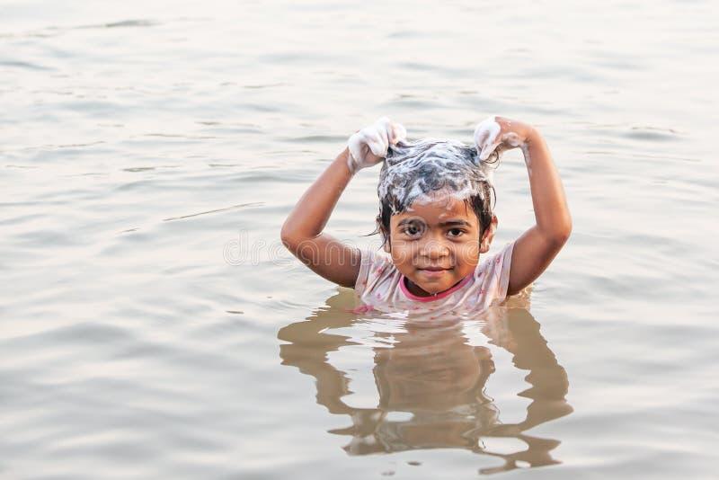 Kleines Mädchen Stamm Bru ist, lächelnd und mit Shampoo beim Nehmen der Dusche im Mekong im heißen Wetter des Sommers Bru-Dorf, lizenzfreies stockfoto