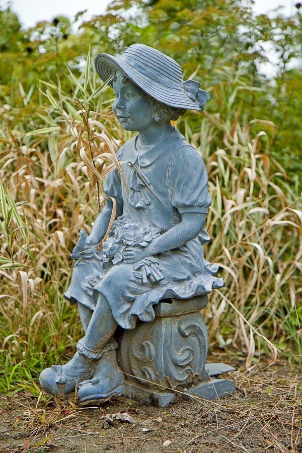 Kleines Mädchen-Statue in sterbendem Garten stockfotos