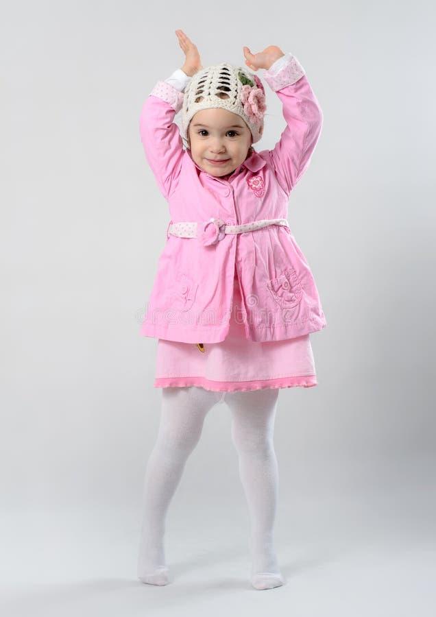 Kleines Mädchen steht auf ihr auf den Zehen gehen und hebt ihre Hände an stockbild