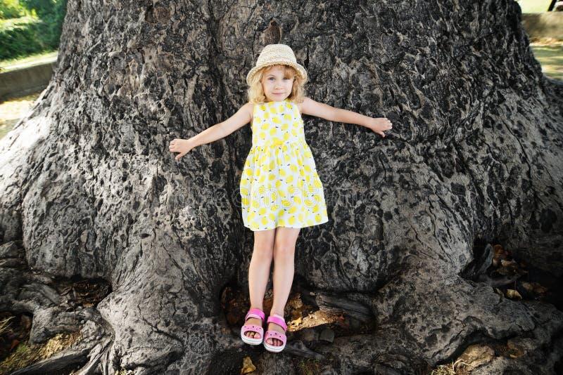 Kleines Mädchen steht an der Basis eines großen Tulpenbaums lizenzfreies stockbild