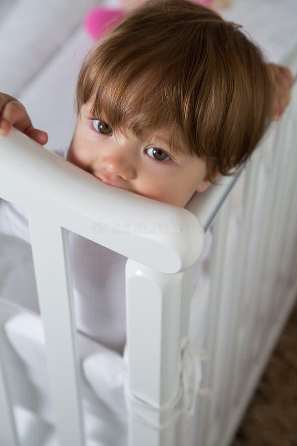 Kleines Mädchen steht im Babyfeldbett stockfotografie