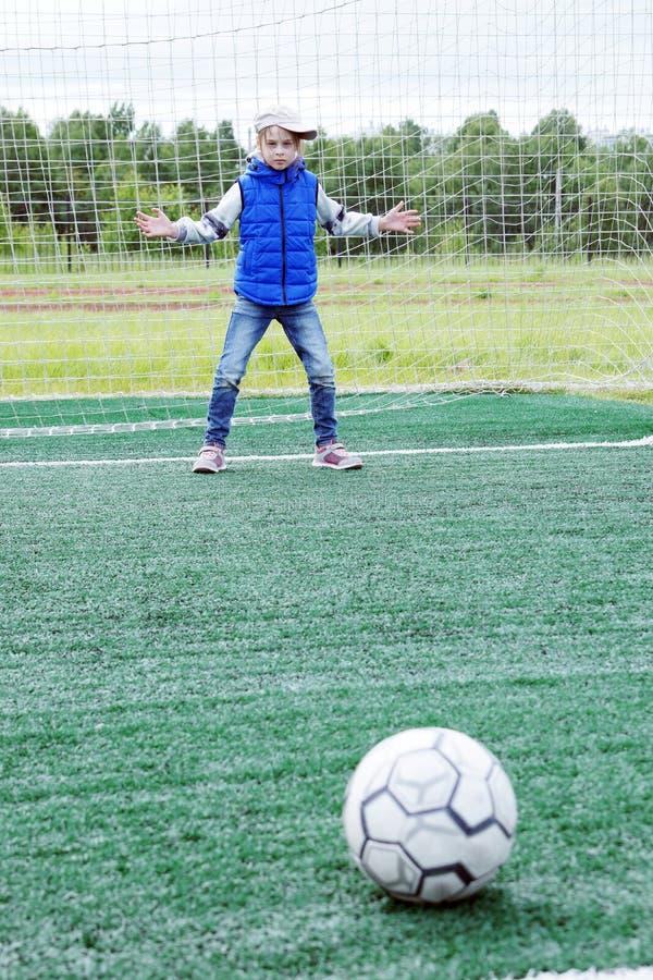 Kleines Mädchen steht im Fußballtor als Torhüter und wird fertig, den Ball zu fangen stockfotografie