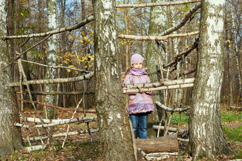 Kleines Mädchen steht im Herbstpark innerhalb des Rahmens lizenzfreies stockbild