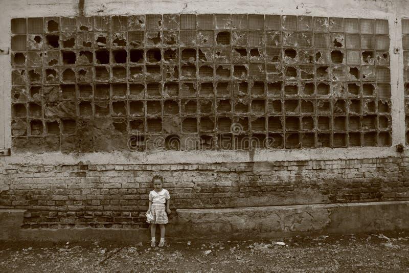 Kleines Mädchen steht nahe der zerstörten Wand lizenzfreie stockbilder
