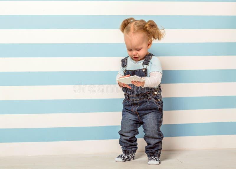 Kleines Mädchen steht nahe einem gestreiften Hintergrund stockfoto