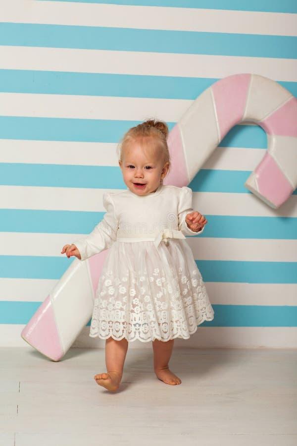 Kleines Mädchen steht nahe einem gestreiften Hintergrund mit einer großen Süßigkeit lizenzfreies stockbild