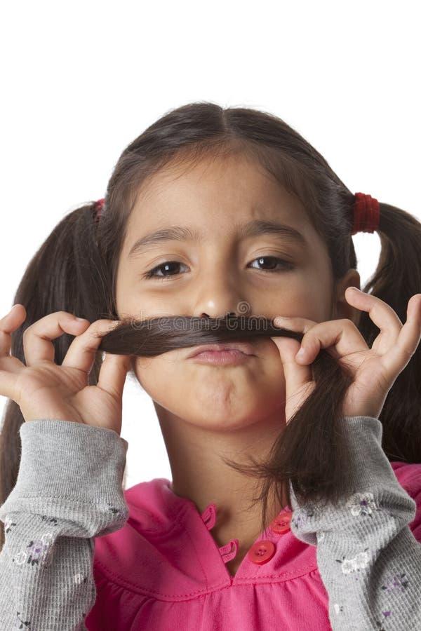 Kleines Mädchen stellt einen Schnurrbart von ihrem Haar her stockfotos