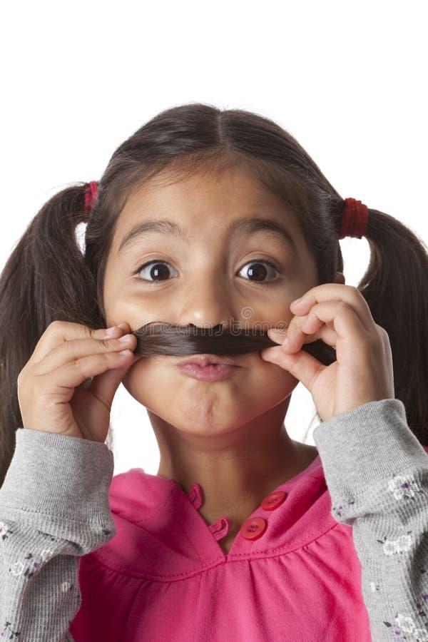 Kleines Mädchen stellt einen Schnurrbart von ihrem Haar her lizenzfreie stockfotografie