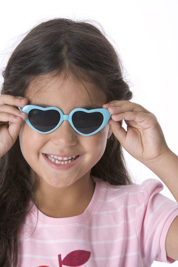 Kleines Mädchen trägt Inneres geformte Sonnenbrillen stockfotos