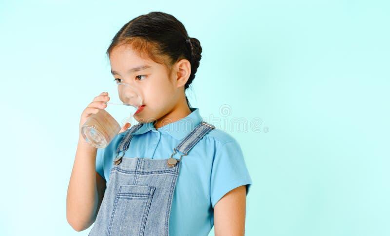 Kleines Mädchen trinkt Wasser auf blauem Hintergrund lizenzfreie stockbilder