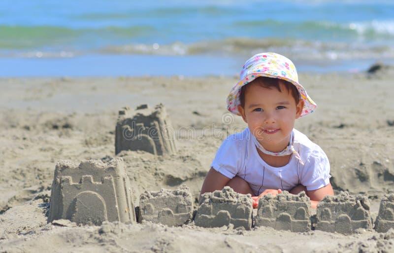 Kleines Mädchen am tropischen Strand, der Sandburg im Sommer macht stockfoto