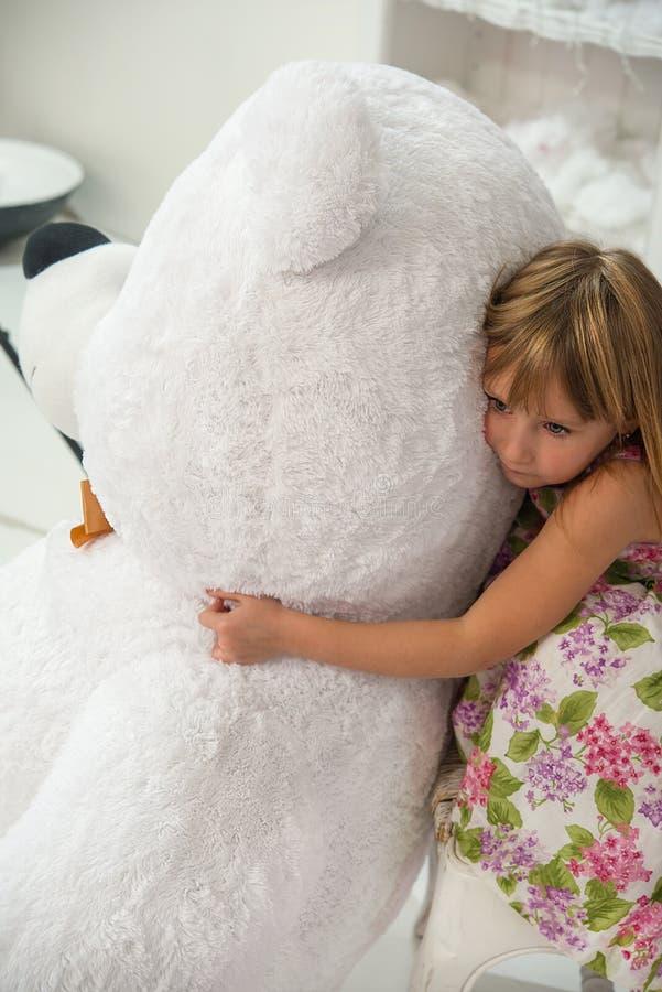 Kleines Mädchen umarmt ein Spielzeug eines großen Teddybären stockbild