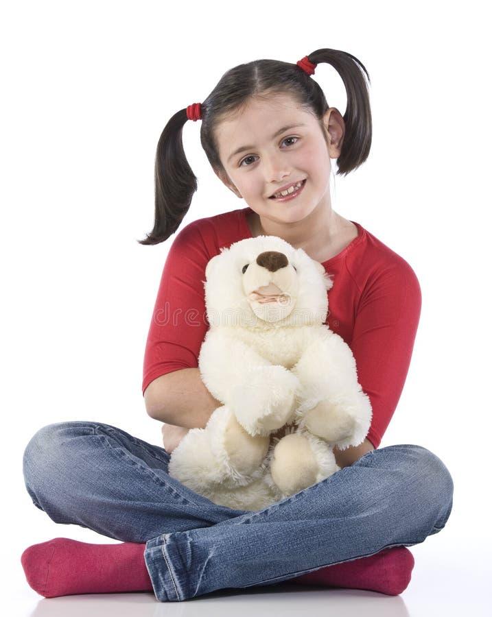 Kleines Mädchen umarmt großen Teddybären stockfoto
