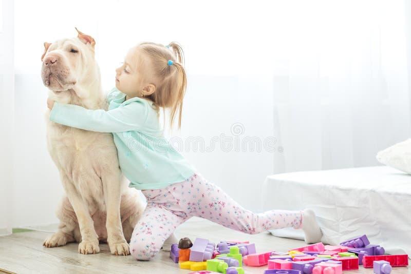Kleines Mädchen umarmt ihren großen Hund Das Konzept des Lebensstils, childhoo lizenzfreie stockfotos