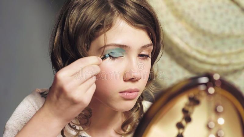 Kleines Mädchen unbeholfen unter Verwendung der Schwesterlidschatten, möchte wie Erwachsener, Nahaufnahme aussehen lizenzfreie stockbilder