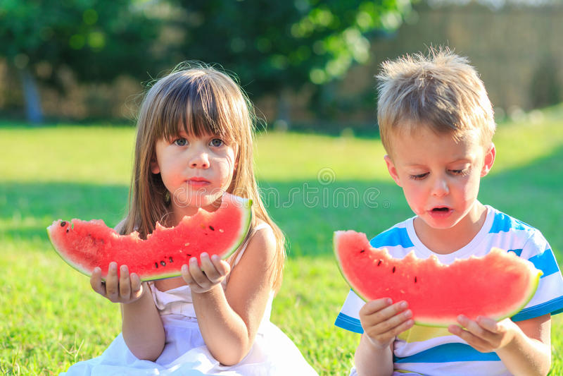 Kleines Mädchen und ein Junge, der Wassermelone isst lizenzfreie stockbilder