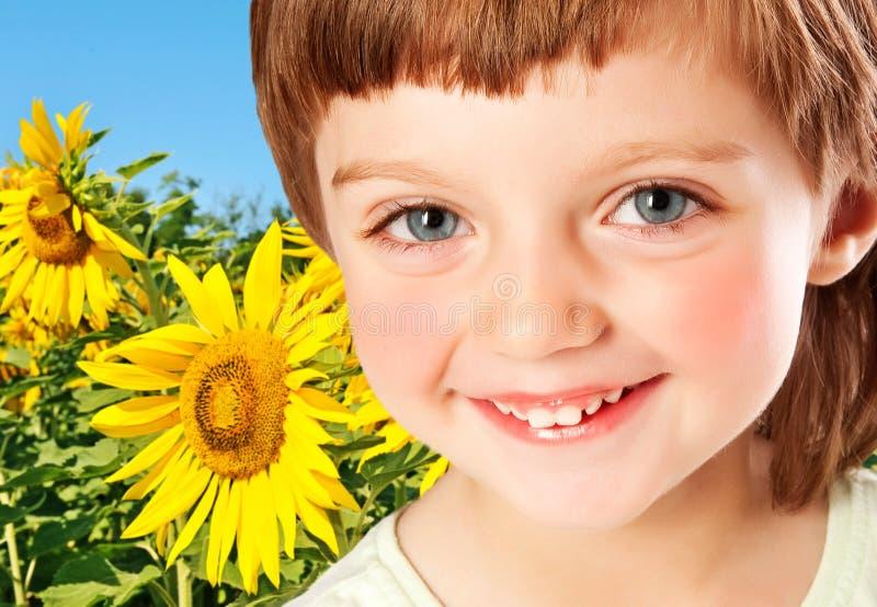 Kleines Mädchen und Feld mit Sonnenblumen lizenzfreie stockfotos