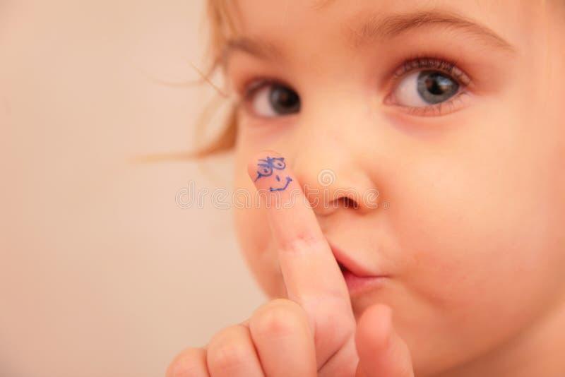 Kleines Mädchen und Finger mit gemaltem Gesicht stockfoto