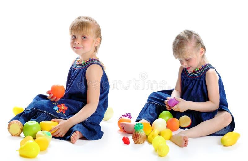 Kleines Mädchen und gefälschte Früchte lizenzfreie stockfotos