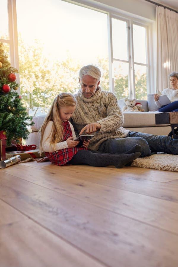 Kleines Mädchen und Großvater mit digitaler Tablette zu Hause lizenzfreie stockfotos