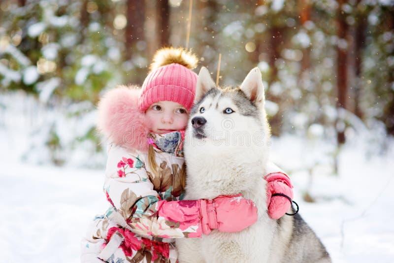 Kleines Mädchen und hasky Hund zusammen im Winterpark stockfotografie