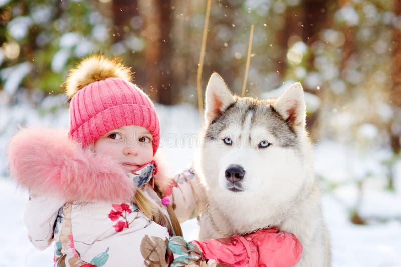 Kleines Mädchen und hasky Hund zusammen im Winterpark stockfoto